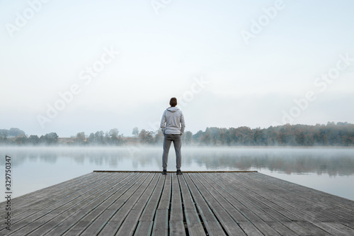 Canvastavla Young man standing alone on wooden footbridge and staring at lake