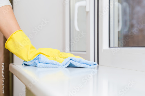 Woman hand in yellow rubber protective glove wiping white plastic window sill from dust with blue dry rag Canvas-taulu