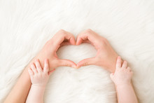 Heart Shape Created From Young Woman Fingers. Infant Hands On Mother Arms. White, Soft, Fluffy Fur Carpet Background. Lovely Emotional, Sentimental Moment. Closeup. Point Of View Shot. Top Down View.