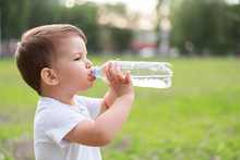 Child Drinks Water From A Bottle On A Hot Summer Day