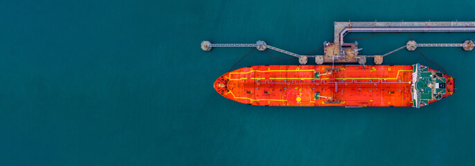 Red cargo tanker ship vessel at port with marine loading arms, Global business oversea commercial trade logistic import export oil and gas petrochemical refinery industry transport worldwide.