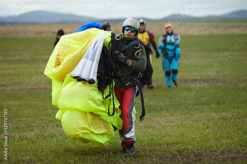 Carta da parati Skydiver, tandem instructor, walks the field with a canopy of a parachute in hands after landing