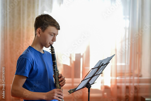 The guy plays the clarinet, looks at the music and plays music in a music school Fototapeta