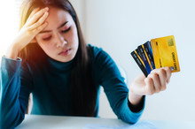 Stressed Young Pretty Woman Headache Holding Many Credit Card In Hand And Worried About Bill In Home Office, Plan Money Cost Saving, Shopping Online, Investment, Business Finance And Expenses Concept