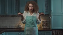 Confused Young Curly Hair 20s Woman With Kitchen Utensil In Hands Shaking Head Hesitantly. Woman Doesn't Know How To Cook And Trow Away Scoop And Ladle.