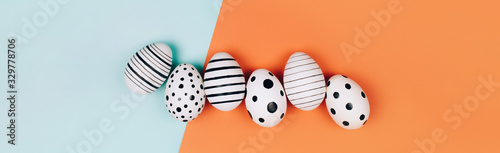 Fotografia Banner made with Easter eggs dotted on multicolored background