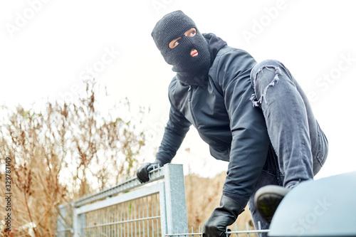 Fototapeta Vermummter Einbrecher klettert über Zaun