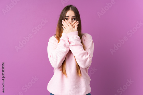 Valokuvatapetti Young caucasian woman isolated on purple background covering mouth with hands