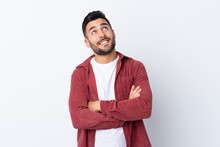 Young Handsome Man With Beard Wearing A Corduroy Jacket Over Isolated White Background Looking Up While Smiling