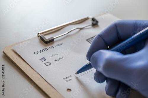Obraz Arzt füllt positiven COVID-19 Test eines Patienten aus - fototapety do salonu
