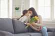 canvas print picture - Happy mothers day. Daughter congratulates hugs his mother holds a bouquet of flowers in the room.