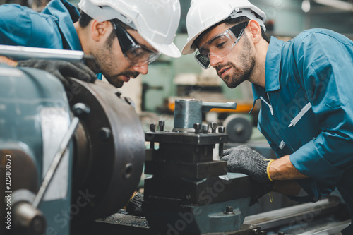 Fotomural Two maintenance engineers discuss inspect relay checking machinery and repair system in a factory