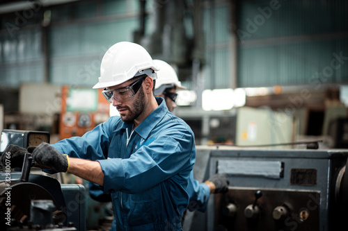 Men industrial engineer wearing a white helmet while standing in a heavy industrial factory behind. The Maintenance looking of working at industrial machinery and check security system setup in factor
