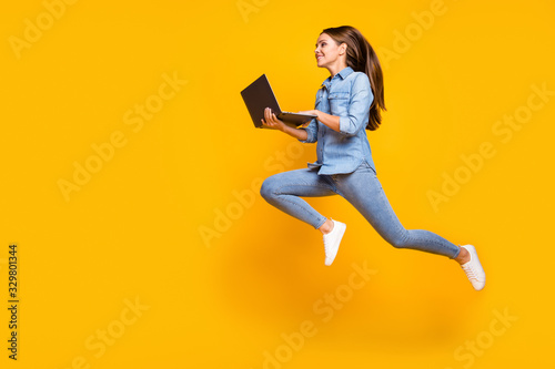 Fototapeta Full body profile photo of pretty business lady jump high holding notebook hands hurry work browsing laptop wear casual denim outfit white sneakers isolated yellow color background obraz na płótnie