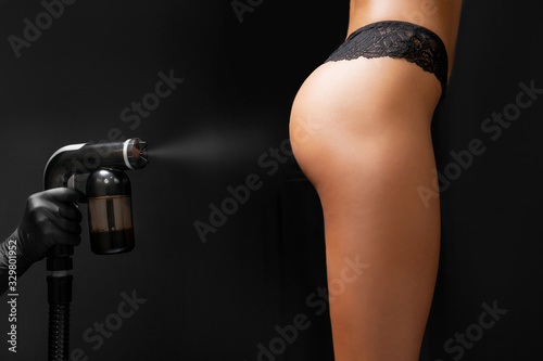 Master applies liquid tan spray for professional athlete woman using airbrush in Canvas Print