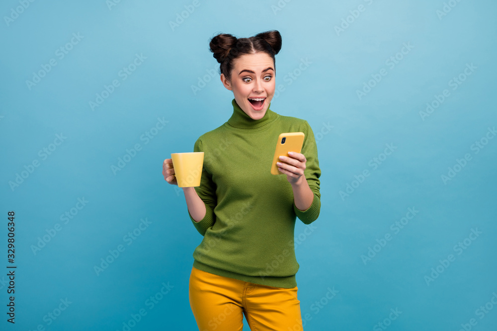 Fototapeta Photo of attractive funny lady hold beverage mug morning freelance work browsing telephone open mouth wear green turtleneck yellow pants isolated blue color background