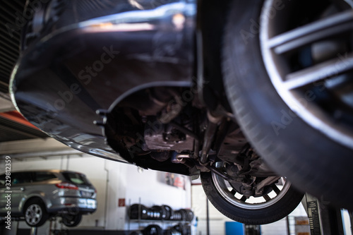 Car in a garage for maintenance, oil/tyre change (shallow DOF; color toned image Wallpaper Mural