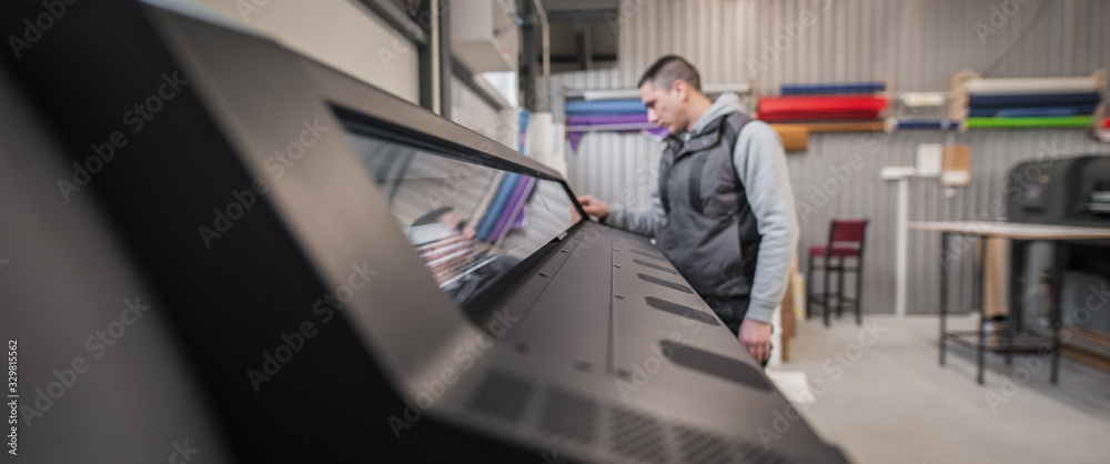 Fototapeta Technician operator checking status on touchscreen front display monitor station