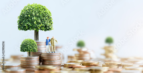 Fototapeta Miniature people: Elderly people sitting on coins stack. social security income and pensions. Money saving and Investment. Time counting down for retirement concept. obraz