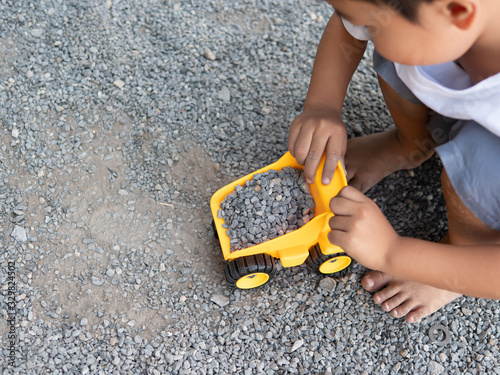 Little child hands playing yellow car truck toy outdoor at home Fototapeta