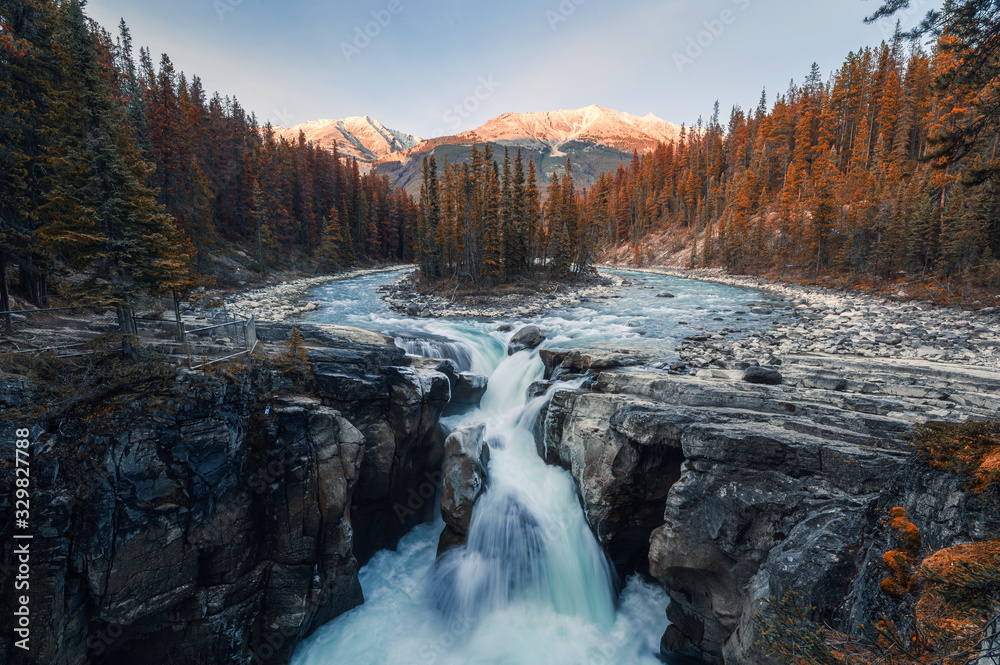 Fototapeta Sunwapta Falls is pair of the Sunwapta river in autumn forest at sunset. Icefields Parkway, Jasper national park
