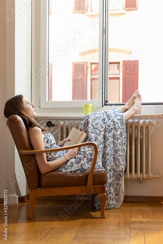 Girl sitting in an armchair near a window reading a book Canvas Print