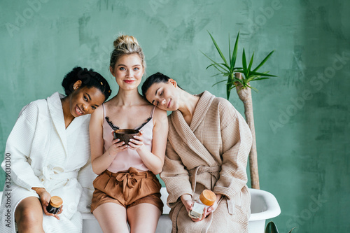 Obraz concept of three different ethnicity of women being very close one to each other and looking naked and expressing friendship on white background - fototapety do salonu