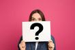 Leinwandbild Motiv Emotional woman holding question mark sign on pink background