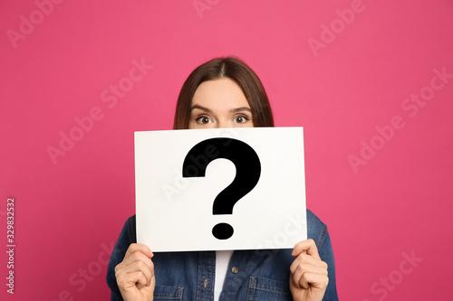 Fototapeta Emotional woman holding question mark sign on pink background obraz