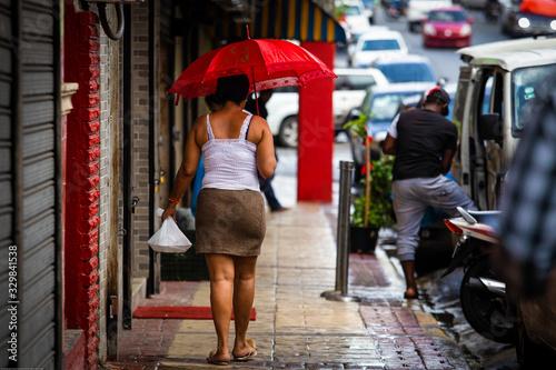 Fotografiet Mujer camina de espaldas. Sombrilla rojo gente en la calle