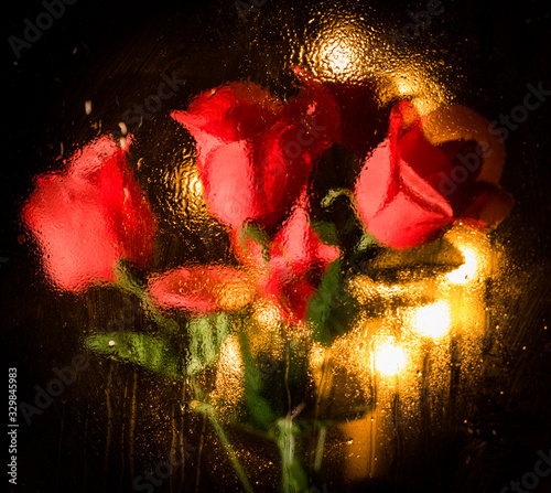 abstract red rose backdrop with rain water drops on glass window