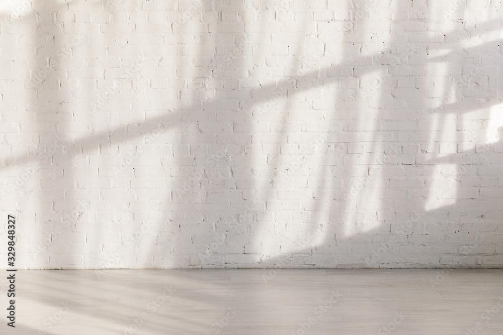 Fototapeta sunlight and shadows on brick wall in empty yoga studio