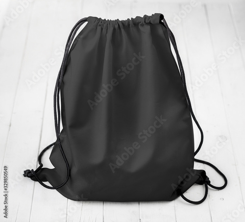 Obraz black backpack with strings on planked surface - fototapety do salonu