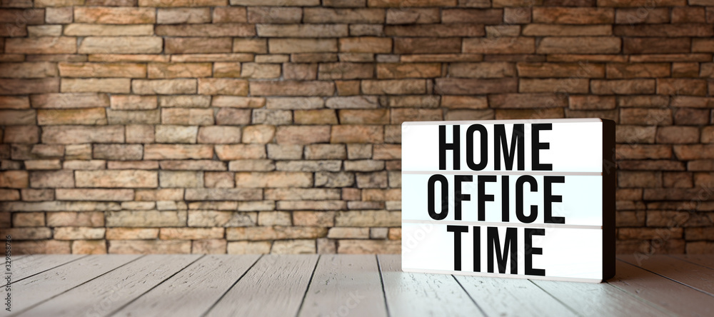 Fototapeta lightbox with text HOME OFFICE TIME in front of a brick wall