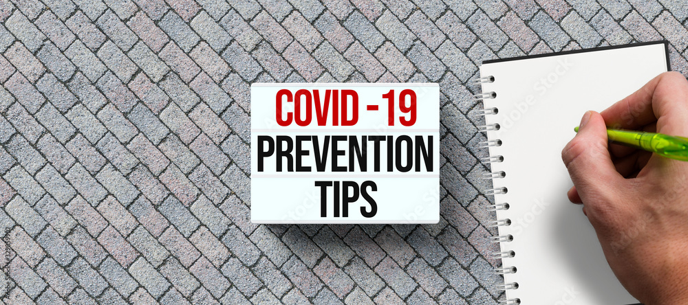 Fototapeta lightbox with text COVID-19 PREVENTION TIPS and hand with pen over a notepad on stone background