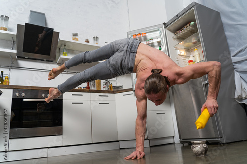 Obraz Muscular man stand on one the hand in the kitchen with bottle of souse. Concept of healthy lifestyle and organic food  - fototapety do salonu