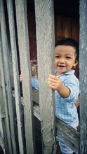 Portrait Of Happy Boy Behind Wooden Fence
