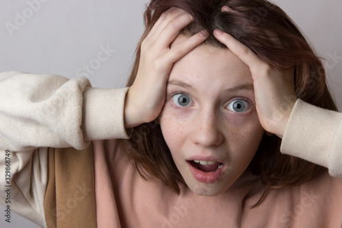 Photo emotional girl with freckles and gray eyes opened her mouth in surprise and horr