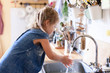 canvas print picture - Kid washing hands at home under water tap. Cute child girl in flour after cooking in cozy home kitchen. Infection prevention. Avoid spreading viruses and germs.