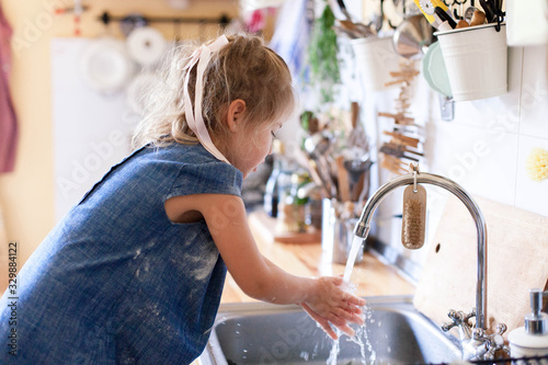Fototapeta Kid washing hands at home under water tap. Cute child girl in flour after cooking in cozy home kitchen. Infection prevention. Avoid spreading viruses and germs. obraz