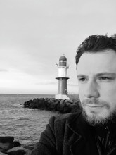 Close-up Of Man Looking Away While Standing Against Lighthouse