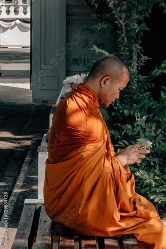 Monk Using Mobile Phone While Sitting On Seat Fototapet