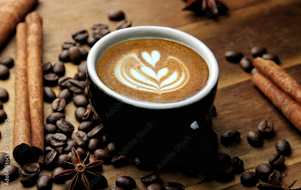 Cup of latte art coffee with roasted beans and cinnamon on wooden background