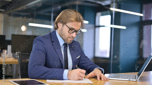 Businessman writing Documents on Office Desk