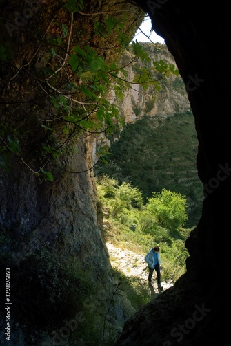 Obraz High Angle View Of Man Seen Through Cave At Barranco Del Infierno - fototapety do salonu