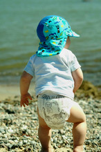 Baby In Cap Walking On Shore At Beach