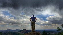 Rear View Of Man Standing On Rock Against Dramatic Sky