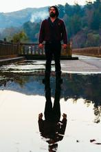 Reflection Of Man Smoking On Puddle During Rainy Season
