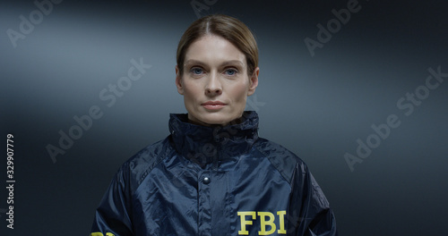 Fototapeta Close up of the young pretty Caucasian woman, FBI worker rising her face and siling happily straight to the camera