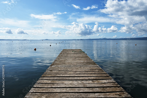 Wooden jetty for boats against a blue sky with some clouds Wallpaper Mural